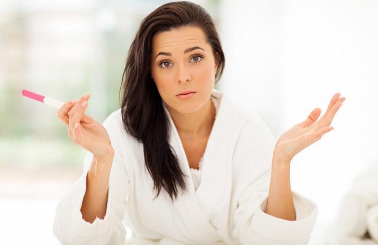 Женщина в замешательстве с тестом на беременность