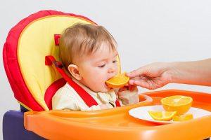 Младенец ест апельсин