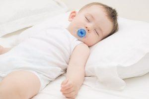 Младенец спит головой на подушке