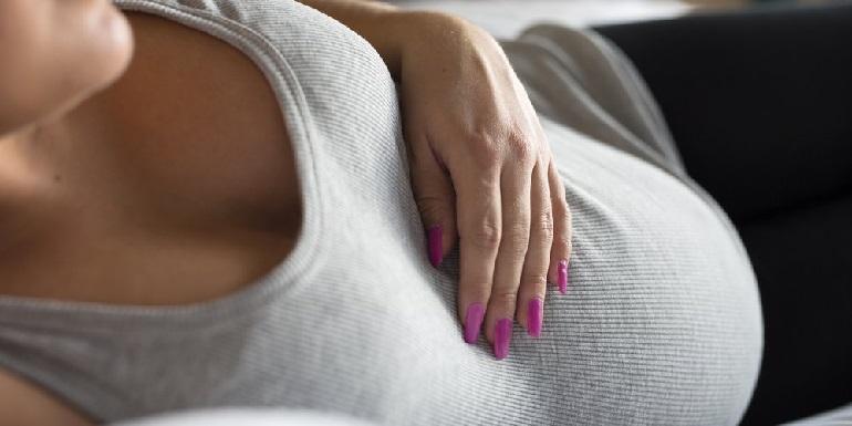 Беременная держится за верх живота